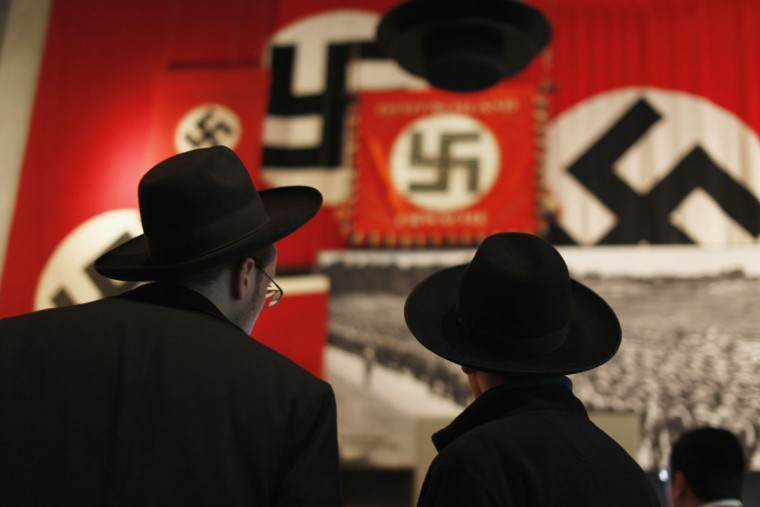 Ultra-Orthodox Jewish visitors look at a display of Nazi flags at Yad Vashem's Holocaust History Museum in Jerusalem January 25, 2013, ahead of International Holocaust Remembrance day which will be marked on January 27. (Reuters/Amir Cohen)
