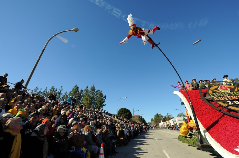 "Acrobats on the Theme Banner float ""Find Your Adventure"" sway over the crowd on flexible poles during the 127th Rose Parade in Pasadena, Calif., Friday, Jan. 1, 2016. (AP Photo/Michael Owen Baker)"