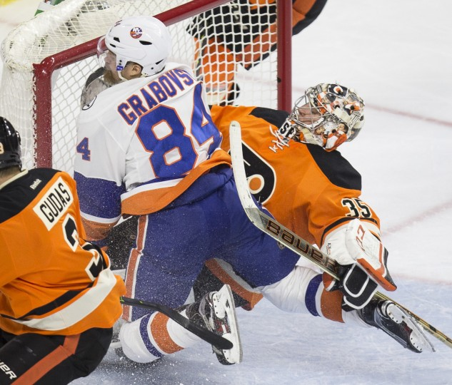 New York Islanders center Mikhail Grabovski (84) collides with Philadelphia Flyers goalie Steve Mason (35) on a play at goal in the second period of an NHL hockey game, Saturday, Jan. 9, 2016, in Philadelphia. (Laurence Kesterson/Associated Press)