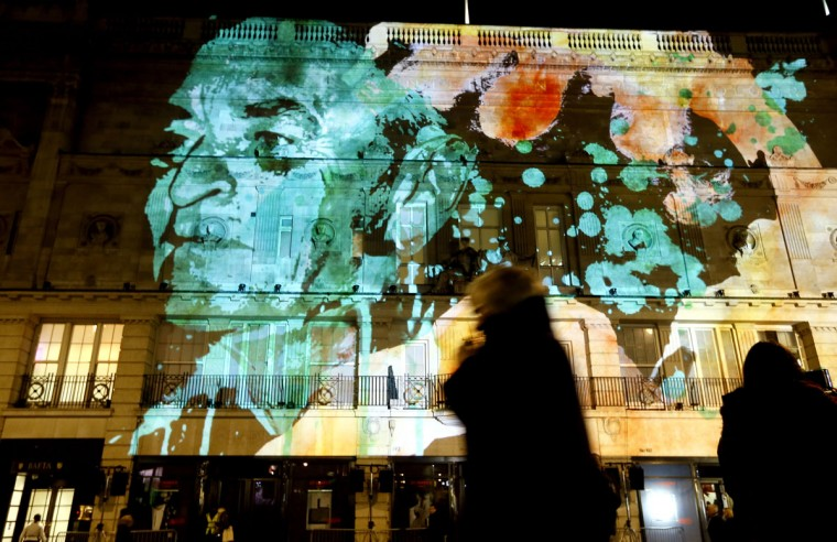 People pass an artwork called '195 Piccadilly' by artist NOVAK in London, Thursday, Jan. 14, 2016. Lumiere London is a festival of lights across 30 London locations, showing installations, projections and interactive pieces, the festival runs until Jan. 17 and is expected to attract thousands of visitors. (AP Photo/Kirsty Wigglesworth)