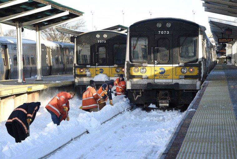 Workers clear the tracks of snow at the Port Washington branch of the Long Island Railroad Monday, Jan. 25, 2016 in Port Washington, N.Y.. Service is suspended on the Port Washington branch due to the recent snow storm. (AP Photo/Kathy Kmonicek)