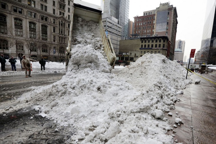 A New York City Dept. of Sanitation truck unloads collected snow for melting, near the World Trade Center site, in New York, Monday, Jan. 25, 2016. East Coast residents who made the most of a paralyzing weekend blizzard face fresh challenges as the workweek begins: slippery roads, spotty transit service and mounds of snow that buried cars and blocked sidewalk entrances. (AP Photo/Richard Drew)