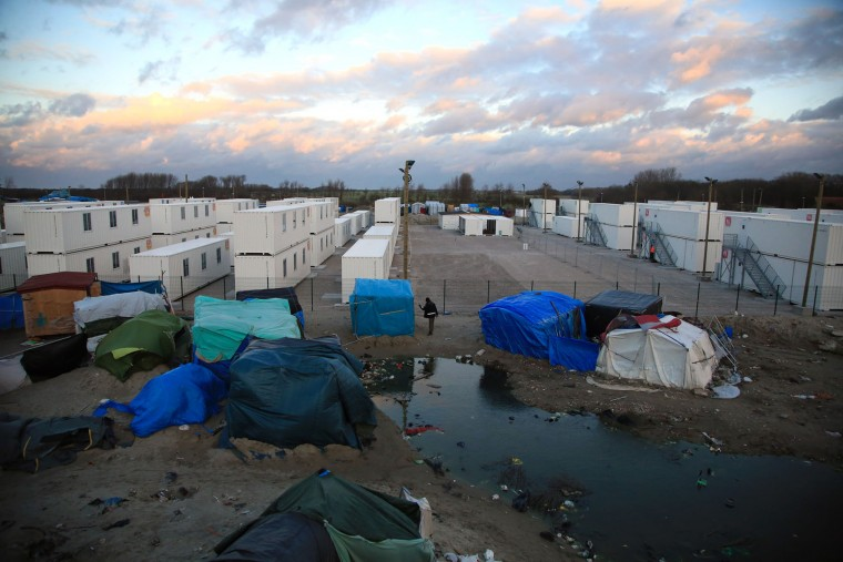 A migrant walks in the migrant camp in Calais, northern France, Wednesday, Feb. 3, 2016. About 4,000 people from Syria, Sudan and other countries are estimated to be camped out in Calais as they try to reach Britain, some recently moving into new facilities but most still sleeping in what's been called Europe's biggest slum. (AP Photo/Thibault Camus)