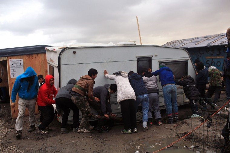 Migrants push a caravan that had fallen down a ditch in the migrant camp of Calais, north of France, Thursday, Feb. 4, 2016. About 4,000 people from Syria, Sudan and other countries are estimated to be camped out in Calais as they try to reach Britain, some recently moving into new facilities but most still sleeping in what's been called Europe's biggest slum. (AP Photo/Thibault Camus)