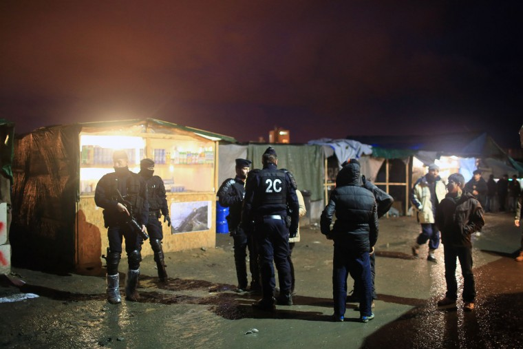 French riot police officers patrol in the migrant camp of Calais, north of France, Thursday, Feb. 4, 2016. About 4,000 people from Syria, Sudan and other countries are estimated to be camped out in Calais as they try to reach Britain, some recently moving into new facilities but most still sleeping in what's been called Europe's biggest slum. (AP Photo/Thibault Camus)