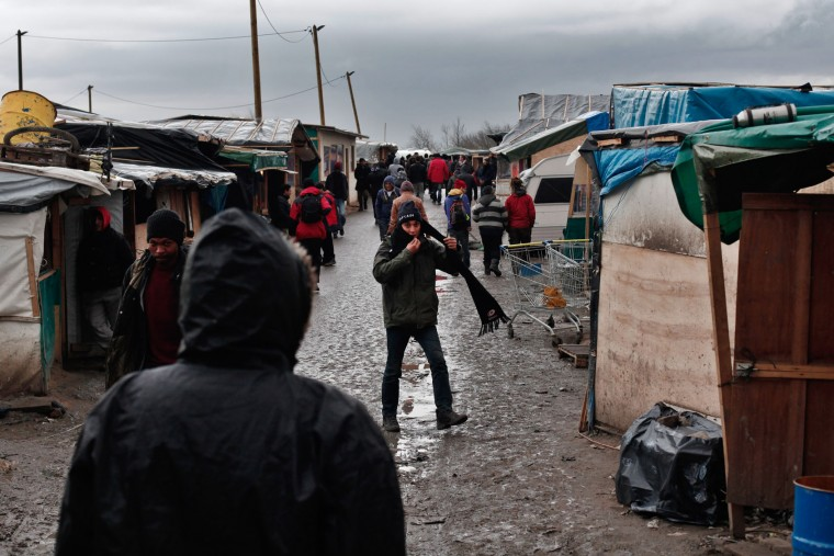 Migrants walk in the main street of the migrant camp of Calais, north of France, Thursday, Feb. 4, 2016. About 4,000 people from Syria, Sudan and other countries are estimated to be camped out in Calais as they try to reach Britain, some recently moving into new facilities but most still sleeping in what's been called Europe's biggest slum. (AP Photo/Thibault Camus)
