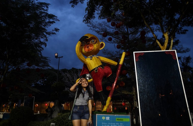A young ethnic Malaysian-Chinese woman poses with a monkey statue at the Fo Guang Shan Dong Zen temple in Jenjarom, on the outskirts of Kuala Lumpur on February 5, 2016, ahead of the Lunar New Year celebrations. The Lunar New Year will mark the start of the year of the monkey on February 8. (Manan Vatsyayana/AFP/Getty Images)