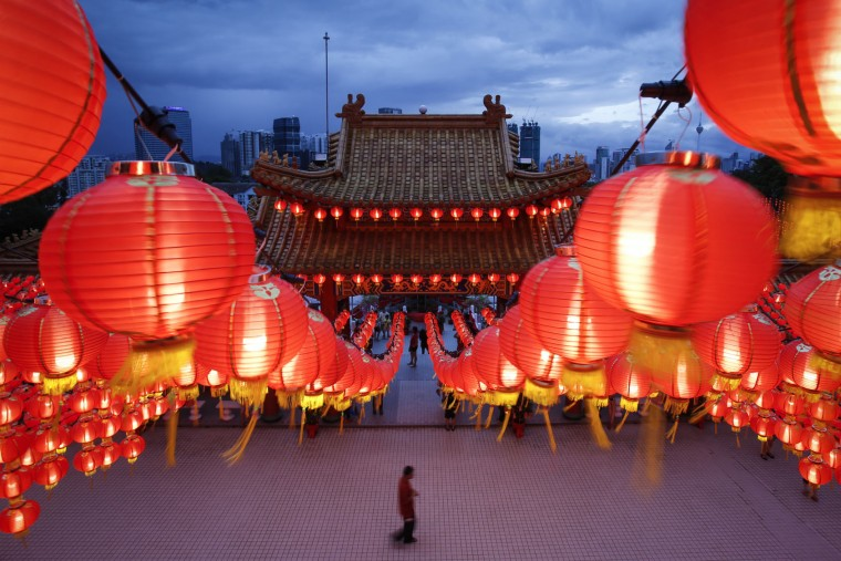 A Malaysian ethnic Chinese man walks under the illuminated traditional Chinese lanterns on the eve of Lunar New Year in Kuala Lumpur, Malaysia, Sunday, Feb. 7, 2016. The Lunar New Year which falls on Feb. 8 this year marks the Year of the Monkey in the Chinese calendar. (AP Photo/Joshua Paul)