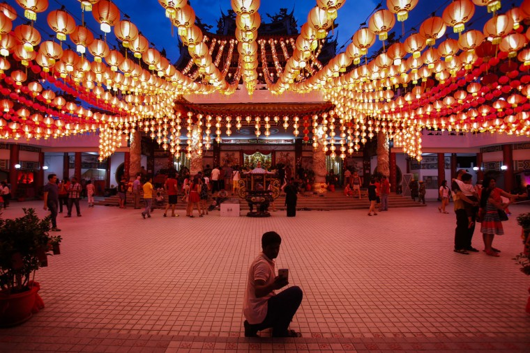 A tourist takes a selfie under illuminated traditional Chinese lanterns on the eve of Lunar New Year in Kuala Lumpur, Malaysia, Sunday, Feb. 7, 2016. The Lunar New Year which falls on Feb. 8 this year marks the Year of the Monkey in the Chinese calendar. (AP Photo/Joshua Paul)