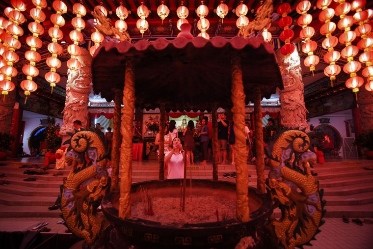 A Malaysian ethnic Chinese woman offer prayers under the illuminated traditional Chinese lanterns on the eve of Lunar New Year in Kuala Lumpur, Malaysia, Sunday, Feb. 7, 2016. The Lunar New Year which falls on Feb. 8 this year marks the Year of the Monkey in the Chinese calendar. (AP Photo/Joshua Paul)