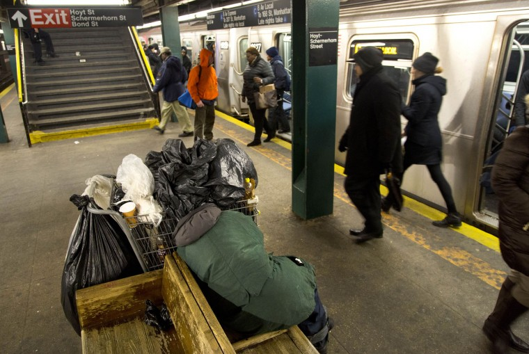 Subway riders walk past a homeless person sleeping on a bench, Tuesday, Feb. 9, 2016, at the Hoyt-Schermerhorn Street station in the Brooklyn borough of New York. As cities nationwide undertake a census of homeless people, perennial concerns arise over the count's reliability. New York City's count took place in freezing weather. (AP Photo/Mark Lennihan)