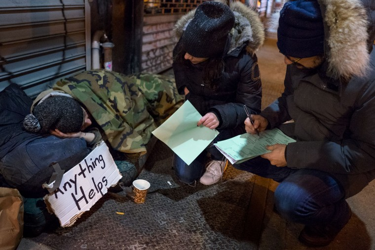 Victoria Parker, center, and Edward Casabian, both of New York and working with The Robin Hood Foundation, an organization that helps the poor, speak to a homeless person as they take part in a count and survey of homeless persons on the streets of New York early Tuesday, Feb. 9, 2016. Hundreds of people fanned out across the city to conduct the survey just after midnight. (AP Photo/Craig Ruttle)