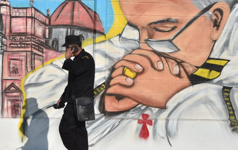 A security member speaks on his mobile phone next to a mural painting depicting Pope Francis in Ecatepec --a rough, crime-plagued Mexico City suburb-- where the latter is to celebrate an open-air mass, on February 14, 2016. Pope Francis has chosen to visit some of Mexico's most troubled regions during his five-day trip to the world's second most populous Catholic country. (Yuri Cortez/AFP/Getty Images)