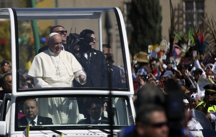 Pope Francis waves from the popemobile upon arrival in Ecatepec --a rough, crime-plagued Mexico City suburb-- where he is to celebrate an open-air mass, on February 14, 2016. The pope has chosen to visit some of Mexico's most troubled regions during his five-day trip to the world's second most populous Catholic country. (Julio Cesar Aguilar Fuentes/AFP/Getty Images)