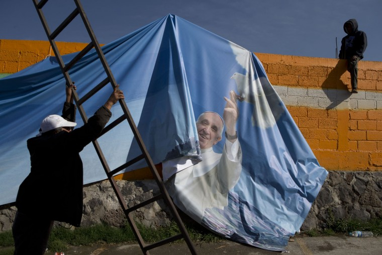 Workers prepare to fix a fallen banner showing Pope Francis holding a dove, on the grounds where Pope Francis was to land by helicopter, in Ecatepec, Mexico state, Mexico, Sunday, Feb. 14, 2016. Pope Francis will give a Mass at an outdoor field in the capital's suburb of Ecatepec to an estimated crowd of 400,000 pilgrims.(AP Photo/Rebecca Blackwell)