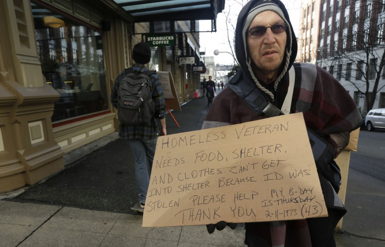 Billy Meyer, who said he has been homeless in both Portland, Ore., and Seattle in the past year, holds a cardboard sign asking for help near a pedestrian bridge leading to the ferry dock in downtown Seattle on Tuesday, Feb. 9, 2016. (AP Photo/Ted S. Warren)