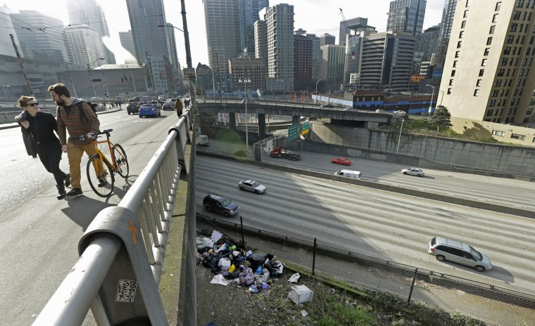 Pedestrians walk above signs of a homeless encampment near a bridge over the Interstate 5 freeway in downtown Seattle on Tuesday, Feb. 9, 2016. Even as homelessness declined slightly nationwide in 2015, it increased in urban areas, including Seattle, New York and Los Angeles. (AP Photo/Ted S. Warren)
