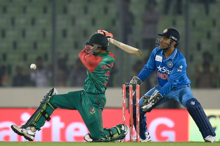 Bangladesh cricketer Taskin Ahmed (L) plays a shot as Indian cricket captain Mahendra Singh Dhoni looks on during the Asia Cup T20 cricket match between India and Bangladesh at Sher-e-Bangla National Cricket Stadium in Dhaka on February 24, 2016. (Munir uz Zaman/AFP/Getty Images)