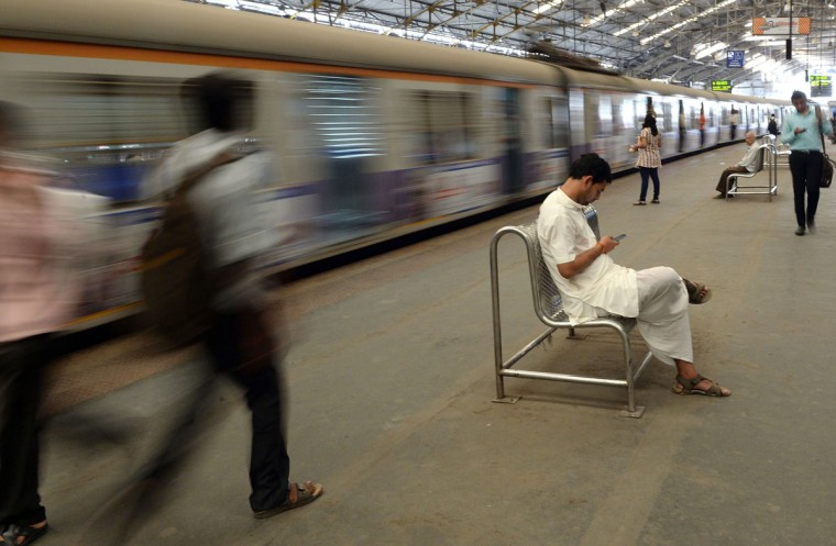 An Indian man checks his mobile phone as a suburban train leaves a station in Mumbai on February 25, 2016. Indian Railway minister Suresh Prabhu announced the Indian Railways Budget on February 25. (INDRANIL MUKHERJEE/AFP/Getty Images)