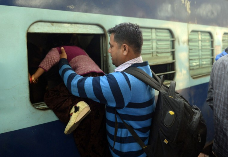 Indian passengers clamber through a window of the packed general wagon of The Simanchal Express at Anand Vihar Railway Station in New Delhi on February 25, 2016. Indian Railways Minister Suresh Prabhu is set to announce the Indian Railways Budget in the country's parliament. (PRAKASH SINGH/AFP/Getty Images)