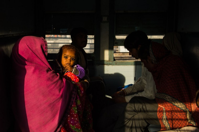 A young Indian child looks on as she sits on her mother's lap inside a train at Hazrat Nizamuddin railway station in New Delhi on February 25, 2016. Indian Railway minister Suresh Prabhu is set to announce the Indian Railways Budget on February 25. (Chandan Khanna/AFP/Getty Images)
