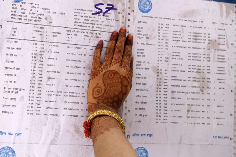 An Indian passenger checks the reservation chart posted on a train carriage at Secunderabad Railway Station in Hyderabad on February 25, 2016, as Indian Railways Minister Suresh Prabhu presents The Railway Budget at Parliament House in New Delhi. (NOAH SEELAM/AFP/Getty Images)