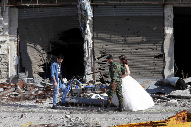 Newly-wed Syrian couple Nada Merhi, 18, and Hassan Youssef, 27, receive instructions from their wedding photographer as they have their pictures taken amid heavily damaged buildings in the war ravaged city of Homs on February 5, 2016. A Syrian photographer thought of using the destruction of Homs to take pictures of newly wed couples to show that life is stronger than death. (Joseph Eid/AFP/Getty Images)
