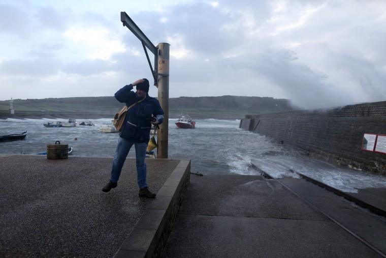 A man stands at the harbor in Auderville, northwestern France, on February 8, 2016, as strong winds hit the region. Winds of over 130 kh/h were recorded in the region where 16 departments have been placed under alert for wind and flooding waves. (CHARLY TRIBALLEAU/AFP/Getty Images)