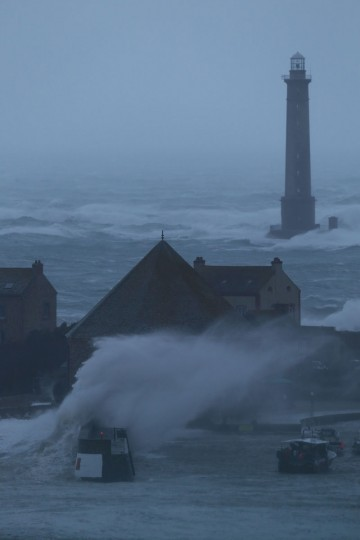 Waves break near the lighthouse in the harbor in Auderville, northwestern France, on February 8, 2016, as strong winds hit the region. (CHARLY TRIBALLEAU/AFP/Getty Images)