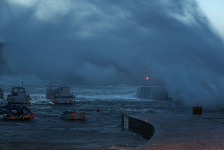 A wave breaks in the harbor in Auderville, northwestern France, on February 8, 2016, as strong winds hit the region. (CHARLY TRIBALLEAU/AFP/Getty Images)