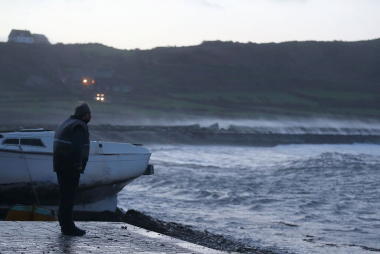 A man watches waves breaking in the harbor of Auderville, northwestern France, on February 8, 2016, as strong winds hit the region. (CHARLY TRIBALLEAU/AFP/Getty Images)