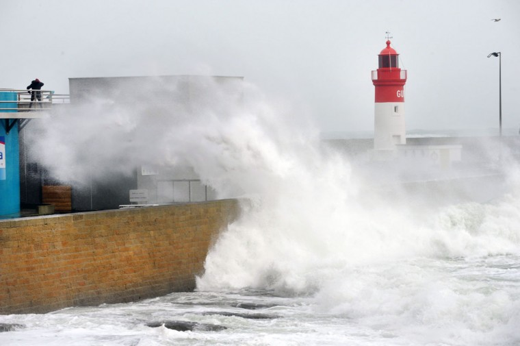 Waves crash against the quay at the light house in the harbor of Lesconil, western of France, on February 8, 2016. (FRED TANNEAU/AFP/Getty Images)