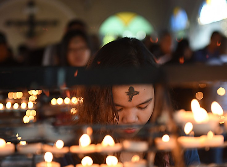 A woman next to lighted candles prays during the observance of Ash Wednesday at a church ground in Manila on February 10, 2016. The 40-day period of Lent begins on Ash Wednesday, with Catholics around the world observing the season which culminates in Easter Sunday. (AFP Photo/Ted Aljibe)
