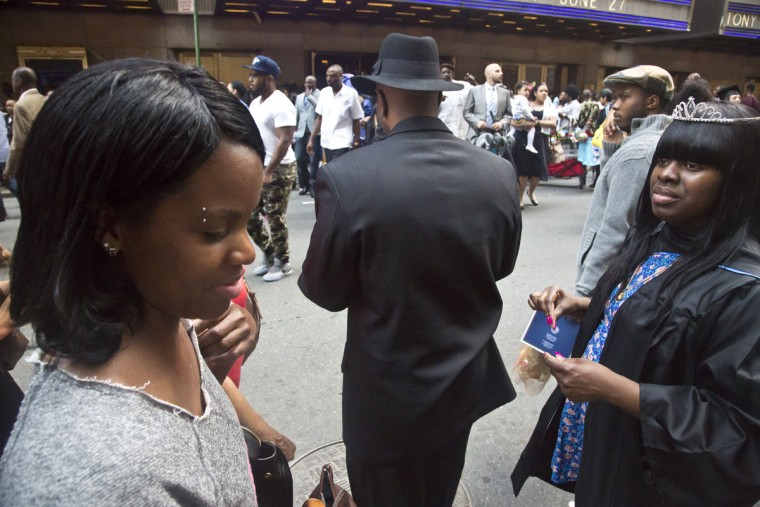 In this June 9, 2015 photo, Candie Hailey, left, talks with her younger sister, Chyna, after her college graduation, as their father Frankie Johnson, center, uses his phone, in New York. After her release from Rikers Island jail, Candie reunited with her younger sisters and father, but dissociated from them as she struggled break free from the trauma of her confinement. (AP Photo/Bebeto Matthews)