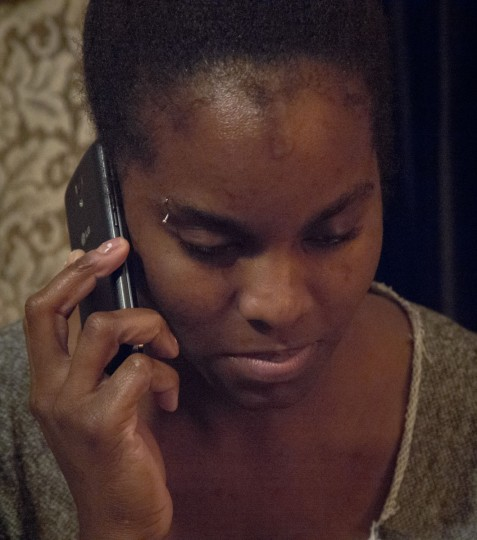 In this Friday, May 22, 2015 photo, Candie Hailey speaks on the phone during a visit to her father's Bronx apartment, which serves as a safe place for her personal items while she stays in a nearby shelter, in New York. In the span of several months since her release from Rikers Island jail, Hailey has struggled to hold onto a phone for a reasonable length of time, with at least five new cellphone numbers underscoring her struggle to recover from the trauma of her solitary confinement. (AP Photo/Bebeto Matthews)