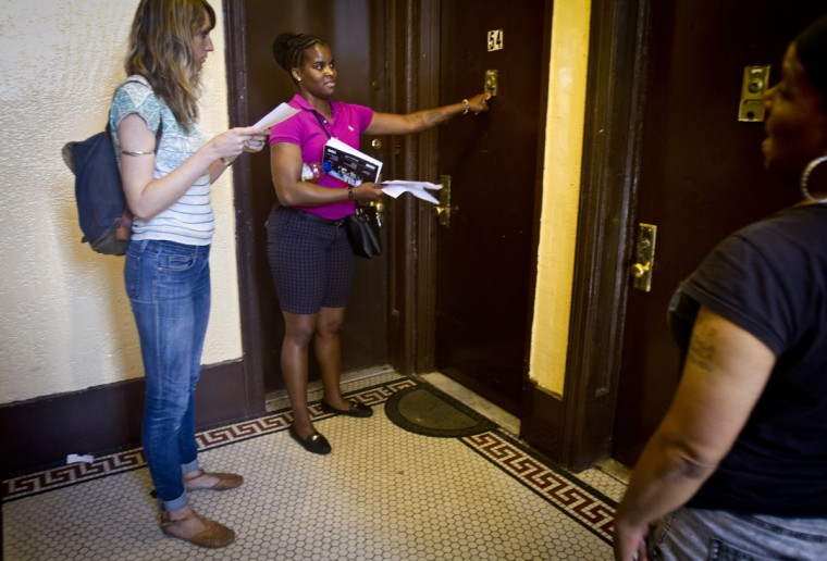 In this Wednesday, Aug. 12, 2015 photo, Candie Hailey, center, accompanied by her social worker, Susan Goodwillie, left, of the Urban Justice Center's (UJC) mental health project, rings the bell at a door while trying to serve court custodial documents to begin a process to see her two young sons, in New York. Noone answered. (AP Photo/Bebeto Matthews)