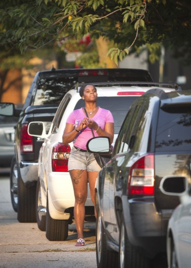 In this Monday, Aug. 17, 2015 photo, Candie Hailey hopes to catch a glimpse of her child as she stands between parked cars as her social worker successfully served court custodial documents at the house where one of Hailey's two sons lives in Freeport, N.Y. After more than three years in jail, 2 1/3 in solitary, Hailey is struggling to break free from the trauma of her confinement and gain footing to be a mother once again. (AP Photo/Bebeto Matthews)