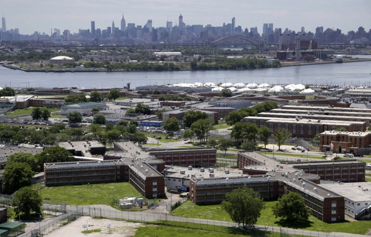 This June 20, 2014 file photo shows the Rikers Island jail complex with the New York skyline in the background. New York City jail officials have recently reformed how solitary in the jails, eliminating its use for young inmates and those suffering from serious mental illnesses. From March 2014 to the end of January 2016, officials have shrunk the overall number of inmates housed in 23-hour confinement from about 600 to 219. (AP Photo/Seth Wenig, File)