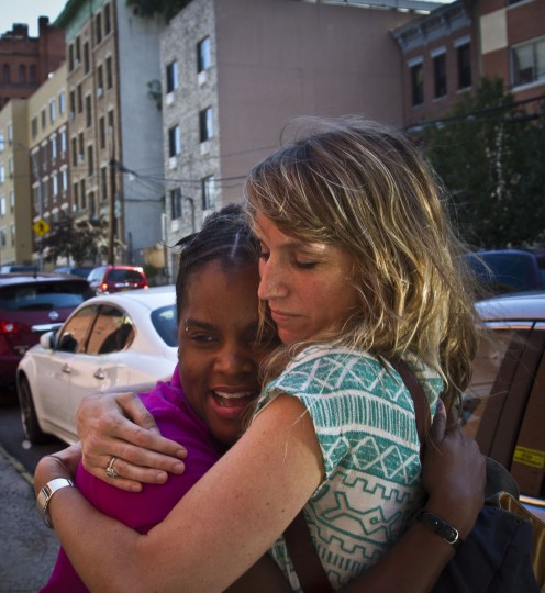 In this Monday, Aug. 17, 2015 photo, Candie Hailey, left, and her social worker Susan Goodwillie, of the Urban Justice Center's (UJC) mental health project, embrace before they set out to serve court documents in a custodial process for one of Hailey's two sons in Freeport, N.Y. After more than three years in jail, 2 1/3 in solitary, Hailey is struggling to break free from the trauma of her confinement with the support of UJC and gain footing to be a mother once again. (AP Photo/Bebeto Matthews)
