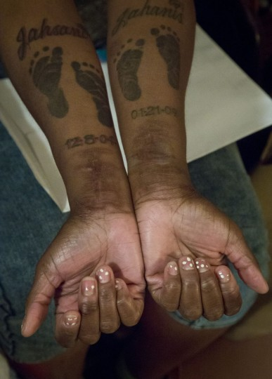 In this Friday, May 22, 2015 photo, Candie Hailey shows her inner forearms with footprint tattoos for her two sons along with their names, and scars on both wrists she says came from suicide attempts while confined at Rikers Island in New York. Hailey was examined after her eight suicide attempts at the jail jail where doctors and psychiatrists say she intentionally hurt herself to escape solitary, where she spent 2 1/3 of three years waiting for a trial. (AP Photo/Bebeto Matthews)
