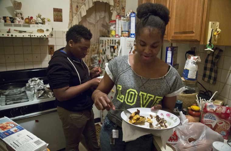 In this Friday, May 22, 2015 photo, Candie Hailey, right, and Timothy, her best friend's brother, eat leftovers while visiting her father's Bronx apartment in New York. For a while after her release from Rikers Island jail, where she spent 2 1/3 years in solitary during her more than three-year incarceration, her father's cooking was a welcomed treat until her struggle to recover from the trauma of confinement caused an estrangement. (AP Photo/Bebeto Matthews)