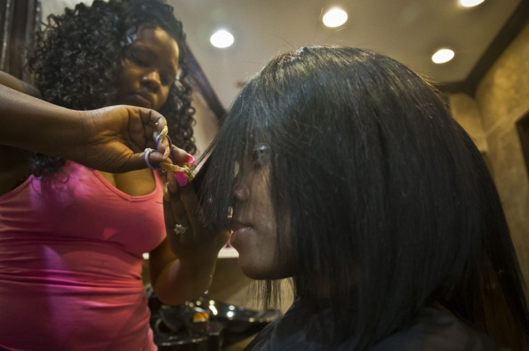 "In this Sunday, May 24, 2015 photo, hairstylist LaTanya Pinckney-Smith, left, works on her friend, Candie Hailey, at Pinckney-Smith's studio in New York, in the Bronx neighborhood where they grew up. ""I love her,"" said Pinckney-Smith. ""She has to look beautiful because I know how it is stereotyping African American women,"" she added, concerned that her friend's upcoming appearance in housing court shouldn't be a negative. Hailey is struggling to regain benefits, including welfare and city and housing, that she lost following more than three years incarceration at Rikers Island, that ended after a jury trial found her not guilty. (AP Photo/Bebeto Matthews)"