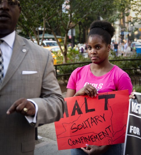 In this Thursday, July 23, 2015 photo, Candie Hailey, right, listens to speakers during a rally against solitary confinement organized by Campaign for Alternatives to Isolated Confinement (CAIC), a coalition of advocates, formerly incarcerated people and their family members in New York. Of her first 19 months in jail at Rikers Island, Hailey served about 17 alone in a 6-by-10-foot cell and had not yet been tried for any crime, let alone convicted. In more than three years in jail waiting on a trial, she spent 2 1/3 in solitary. When she finally went to trial jurors took two days to come back with their verdict: not guilty. (AP Photo/Bebeto Matthews)