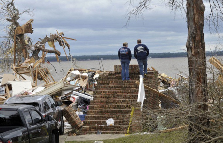 A couple surveys the damage to a property in Pensacola, Fla., Wednesday, Feb. 24, 2016, after a powerful storm affected the area. The National Weather Service is surveying the damage to determine if it was caused by a tornado. (Tony Giberson/Pensacola News Journal via AP)
