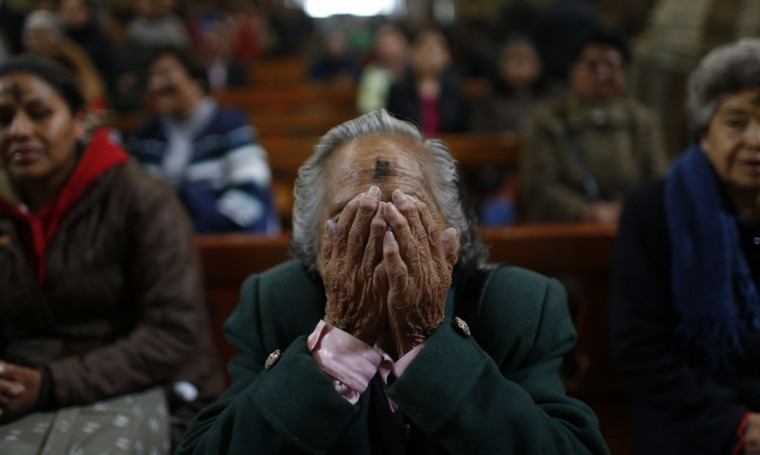 A woman covers her face during prayer while she attends Ash Wednesday Mass at the San Francisco church in La Paz, Bolivia, Wednesday Feb. 10, 2016. Ash Wednesday for Catholics worldwide ushers in a period of penitence and reflection, known as the season of Lent, that leads up to Easter Sunday. (AP Photo/Juan Karita)