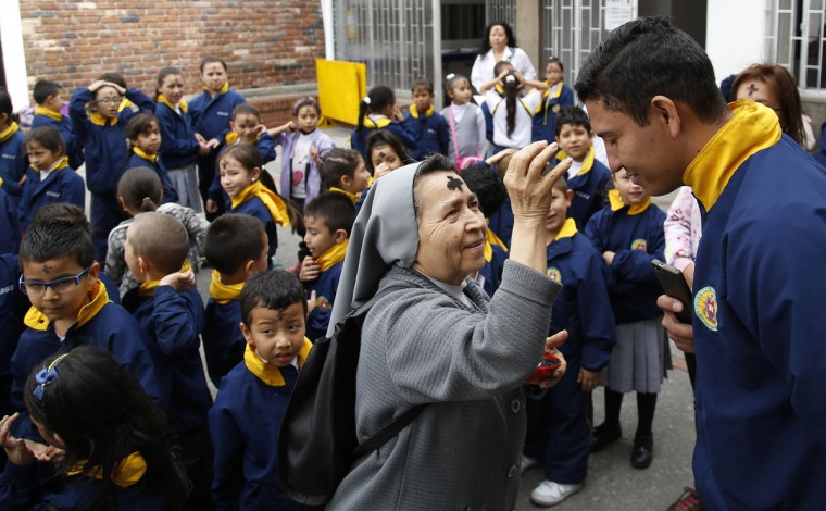 Catholic nun Teresita Padilla places ashes in the shape of a cross on a teacher's forehead during Ash Wednesday in Bogota, Colombia, Wednesday, Feb. 10, 2016. Ash For Christians the ritual marks the start of Lent, a period of penitence, that leads up to Easter. (AP Photo/Fernando Vergara)