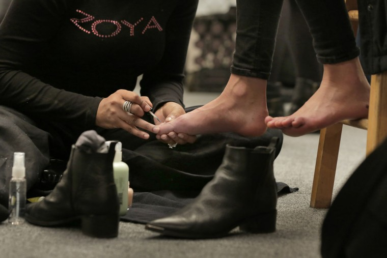 A model gets a pedicure backstage before the BCBG MAX AZRIA Fall 2016 collection is modeled during Fashion Week in New York, Thursday, Feb. 11, 2016. (AP Photo/Richard Drew)