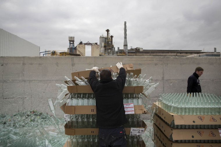In this Wednesday, Jan. 27, 2016 photo, workers unload defective glass bottles to be recycled at the Phoenicia Glass Works Ltd. factory in the southern Israeli town of Yeruham. Factory workers grind these rejects into shards and pile them outside. Recycled glass bottles from across the country are sent here and ground up, too. The glass pieces are shoveled into the ovens to be fired into new glass bottles. Sand, the basic ingredient of glass, is hauled in from a nearby desert quarry. (AP Photo/Oded Balilty)
