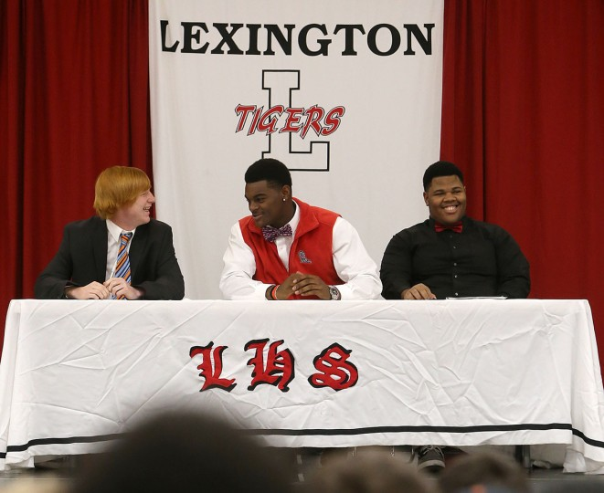 Football players Ryan Courtright, left, Tariqious Tisdale and Michael Hicks smile before signing their letters of Intent during national signing day at Lexington High School, Wednesday, Feb. 3, 2016, in Lexington, Tenn. Courtright, a punter/kicker, committed to the University of Tennessee at Martin. Tisdale committed to Mississippi as a linebacker. Hicks, an offensive lineman, committed to the University of Central Missouri. (C.B. Schmelter/The Jackson Sun via AP)