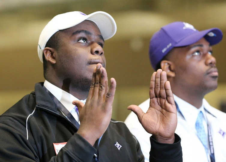 Pace Academy football player Jordan Harris, left, signals touchdown as he and Timothy Coleman, right, discuss going to Furman during national signing day at the College Football Hall of Fame, Wednesday, Feb, 3, 2016, in Atlanta. (Curtis Compton/Atlanta Journal-Constitution via AP)